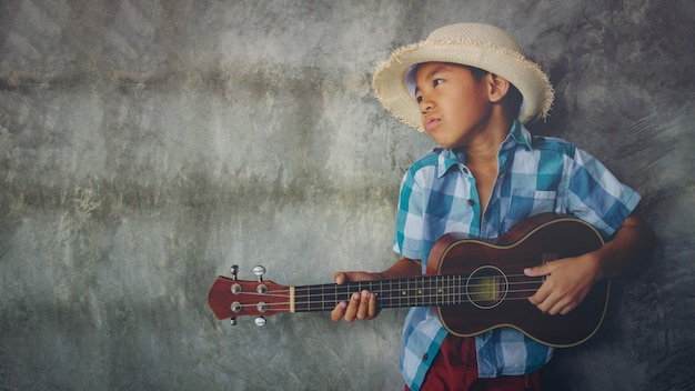 Asian boy aged 5-6 play ukulele cool gesture passionate love in music empty space