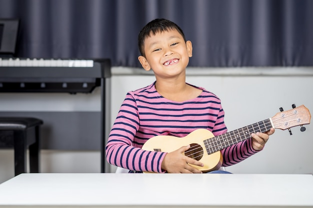 Asian boy  aged 7-8 play ukulele in the room, passionate love in music