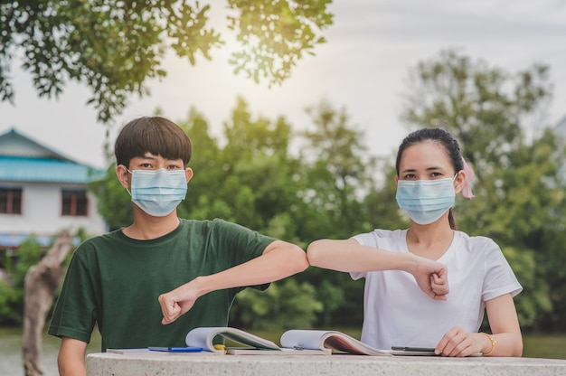 アジアの男の子と女の子が学校に戻って身に着けているフェイスマスクと握手は、新しい通常の社会的な距離に触れないでください