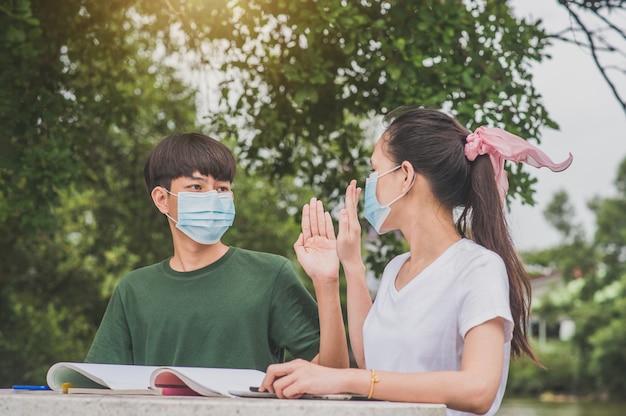 Азиатские мальчик и девочка возвращаются в школу в маске для лица и пожимают друг другу руки, сохраняя новую норму, не прикасаясь к социальному дистанцированию