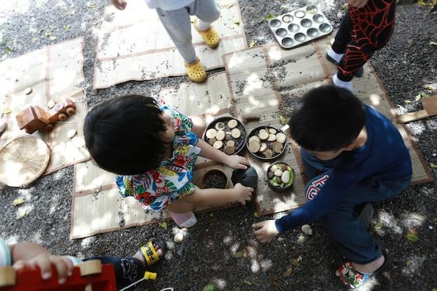 庭、ホームスクール、ウォルドルフ教育の概念で木のおもちゃで遊ぶアジアの男の子と女の子。