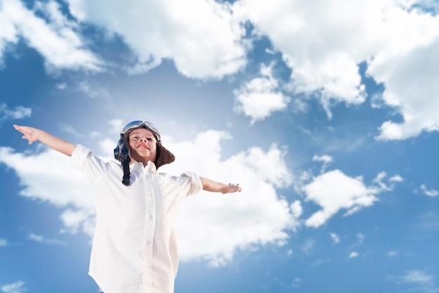 Asian boy in aviator hat posing flying