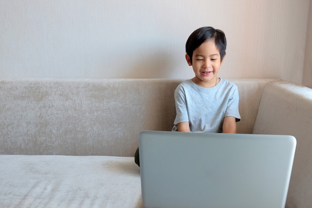 Asian boy child sitting on sofa and uses laptop for education