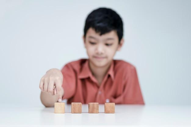아시아 소년은 나무 큐브, 교육 개념, 그리고 새로운 표준에서 학습을 선택합니다.