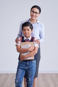 アジアの少年が論文を握りしめ、肩に手で後ろに立っているメガネの女性