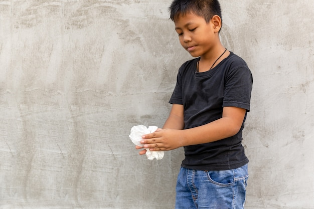 Asian boy cleaning his hands with wet tissue.