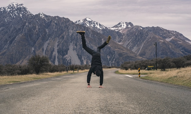 An asian boy doing back flip outdoor on the road with snow mountain