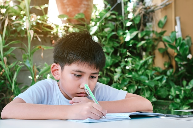 Asian boy doing his homework using a pen to write on a notebook.
