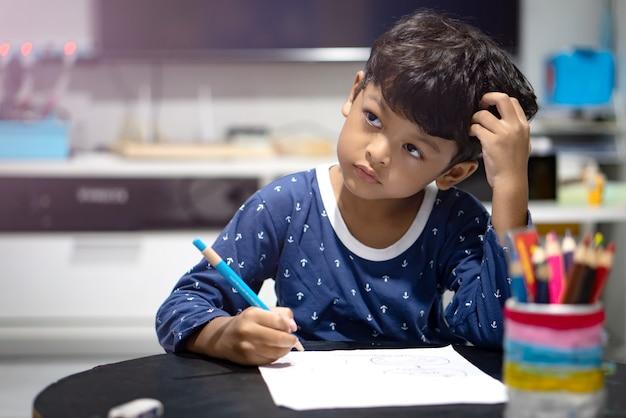 就寝前に宿題やワークシートをやっているアジアの少年。
