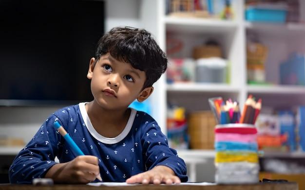 Asian boy doing homework or work sheet before bedtime.