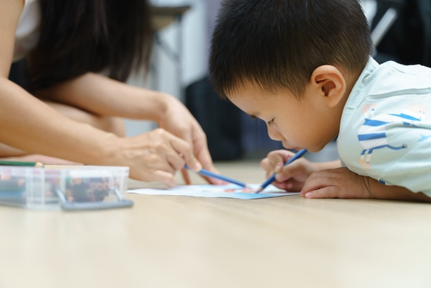 アジアの少年の描画と彼の母親と一緒に絵