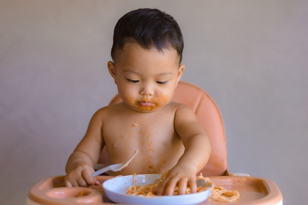 Asian boy eatting on high baby chair.