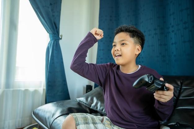 アジアの少年は自宅のリビングルームで興奮して非常に楽しいビデオジョイスティックと一緒にビデオゲームを楽しむ