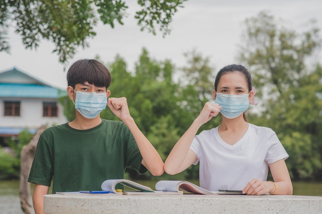 Asian boy and girl back to school a wearing face mask and shake hands keep new normal no touching social distancing