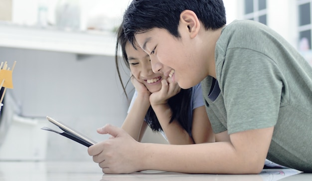 Asian boy and girl playing game on mobile phone together with smile face.