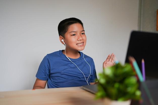 Азиатский мальчик приветствует друзей и учителя, пока присоединяется к школьному электронному обучению