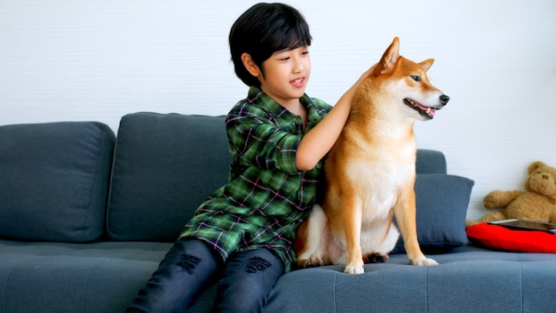 Asian boy having fun playing with his dog on sofa at home.