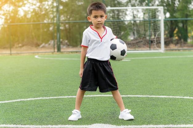 Азиатский мальчик держит футбол на футбольном поле.