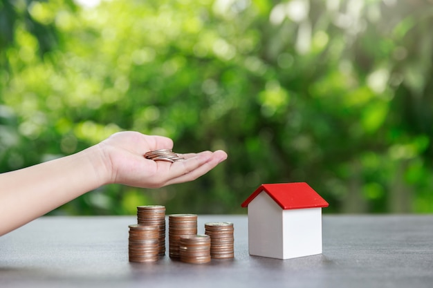 Asian boy holding money and coin stack with house model on green.