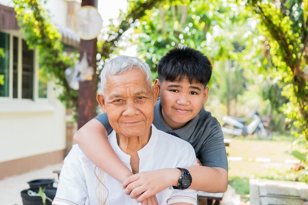 Asian boy hugging living with retired grandfather. nephew or grandson playing smile together looking at camera in home outdoor, happy family members relationship / father and dad day concept, 4k shot