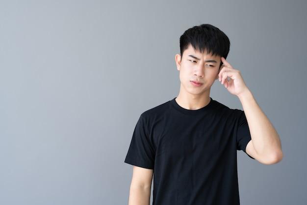 立っている黒いtシャツのアジアの少年