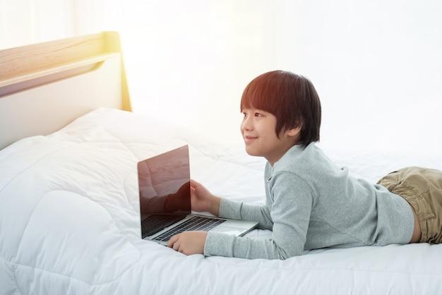ラップトップコンピューターの前でアジアの少年は笑顔でベッドに横たわっていた。