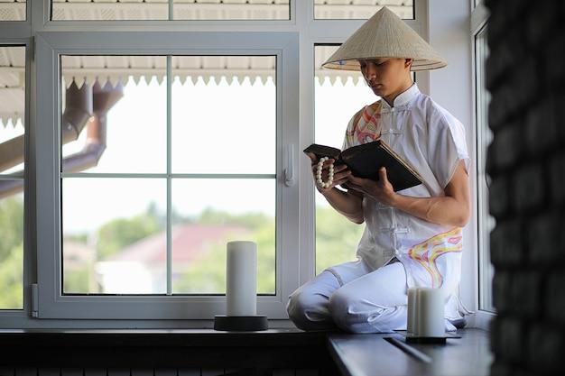 Азиатский мальчик в кимоно читает старую книгу, сидя у окна