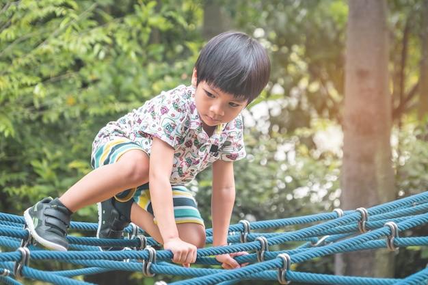 놀이터에서 밧줄 다리에 아시아 소년 등반