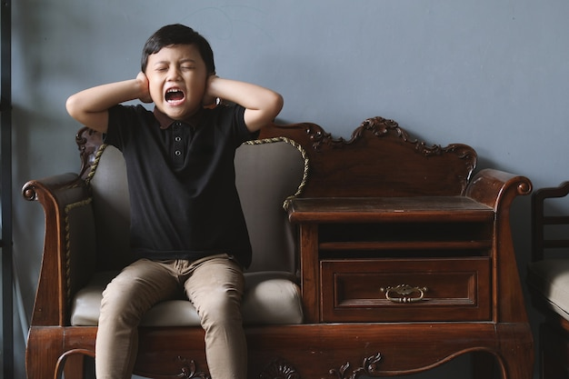 An asian boy is crying and screaming on the sofa while covering his ears and closing his eye