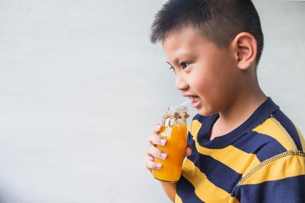 An asian boy is drinking a bottle of orange juice.