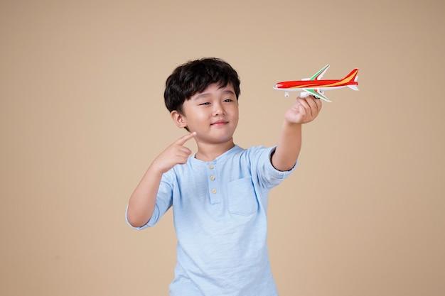 アジアの少年はベージュで隔離の飛行機のおもちゃで旅行するのが楽しみです