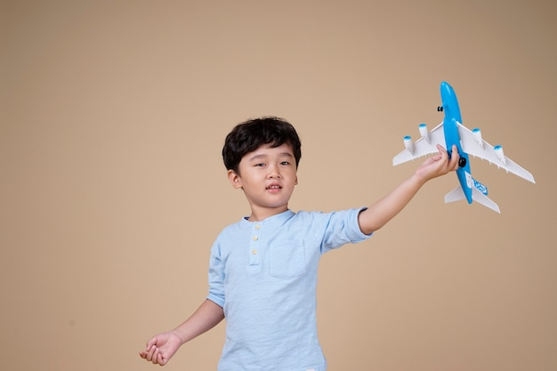 Asian boy is exciting to travel on airplane toy isolated on beige