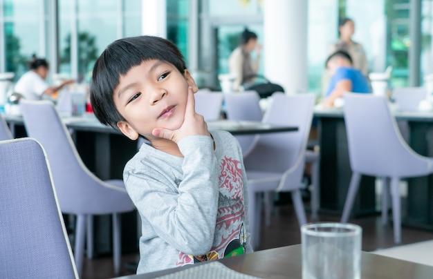 Asian boy is having breakfast in cafe