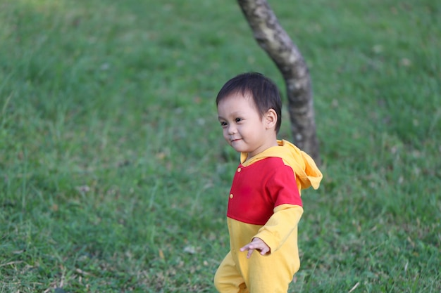 Asian boy is learning to walk in the garden.