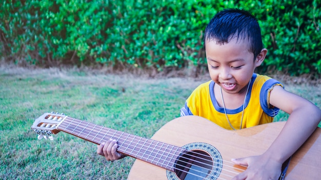 An asian boy is playing an acoustic guitar in a garden with green trees.