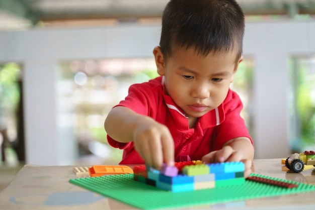 Asian boy is playing building blocks