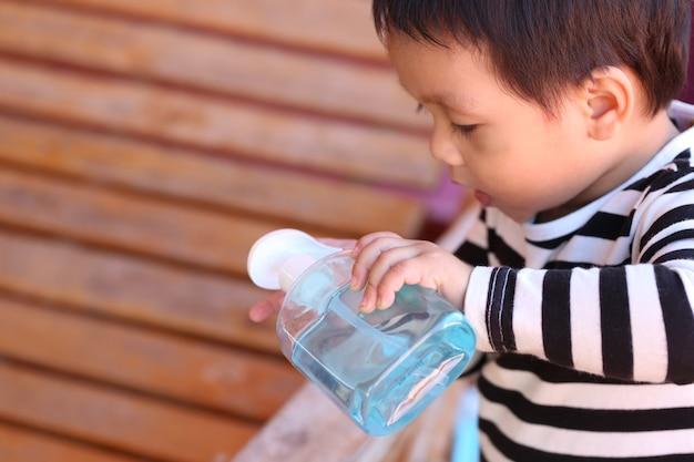 Asian boy is pressing an alcohol gel