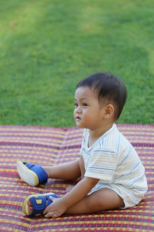 Asian boy is sitting in the garden, cuteness of the toddler