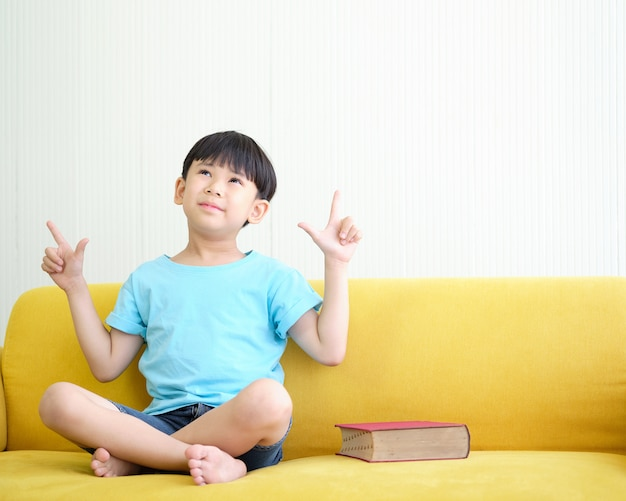 Asian boy is sitting on a yellow sofa with a book that is near place