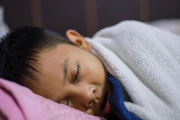 Азиатский мальчик хорошо спит на матрасе и одеяле в своей спальне. сладкие сны
