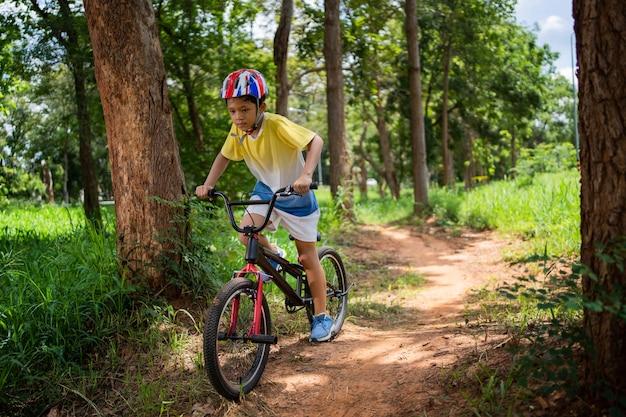 アジアの少年は幸せなマウンテンバイクのトレーニングをしています。