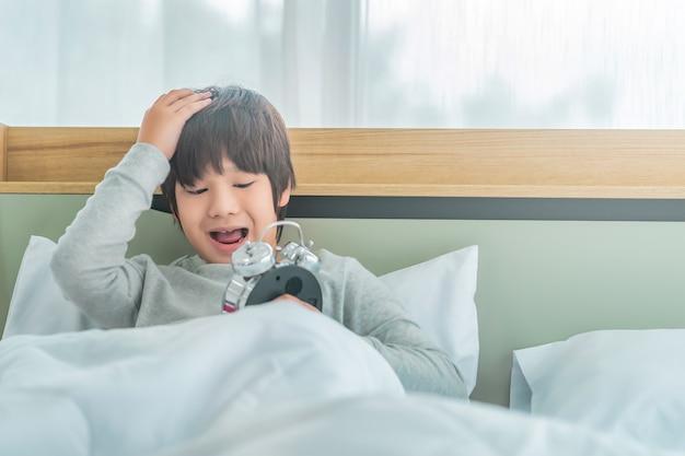 アジアの少年は、ストレスと欲求不満の不眠症の概念で、朝、自宅のベッドの目覚まし時計で目を覚ますことに腹を立てています。