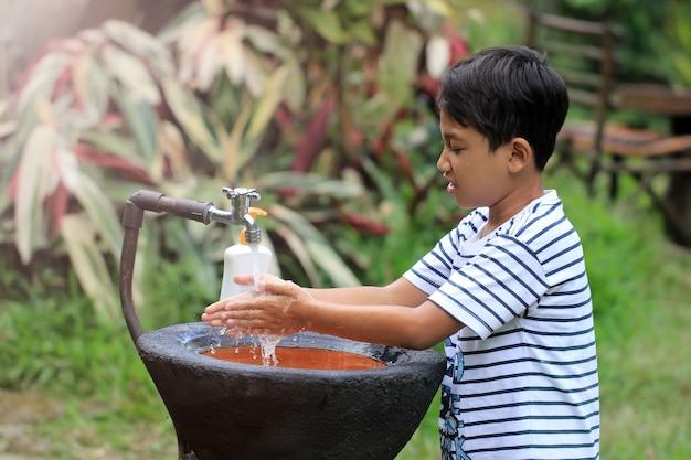 アジアの少年は屋外のシンクで手を洗っています。
