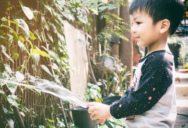 Asian boy is watering plant in his garden