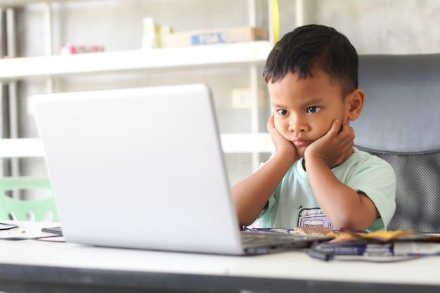 Азиатский ребенок мальчик сидит за столом с ноутбуком и готовится к школе. концепция онлайн-образования. изучение уроков онлайн-видеоконференцсвязи.