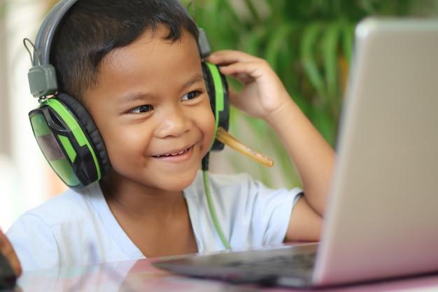 아시아 소년 아이는 테이블에 노트북을 들고 앉아 학교에 갈 준비를 합니다. 온라인 교육 개념입니다. 온라인 화상 통화 회의 수업 수업 연구.