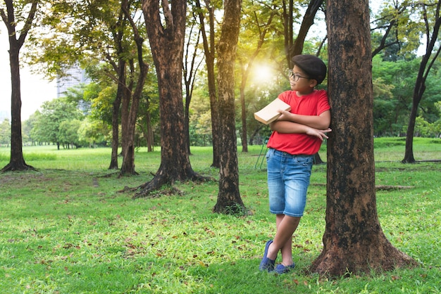 Asian boy leaning against the big tree in public park, a book in hand