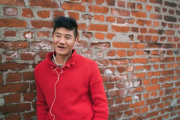 Ragazzo asiatico che ascolta la musica con gli auricolari.