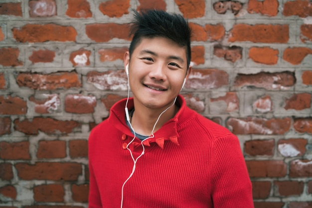 Asian boy listening to music with earphones.