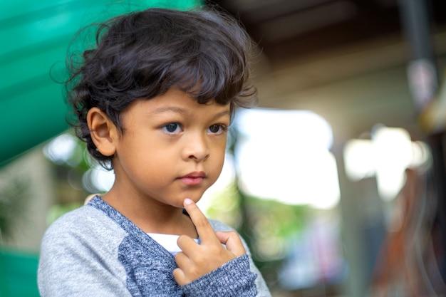 アジアの少年は楽しみにしてアイデアを出します。